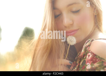 beautiful blonde on the outside with dandelion girl with beautiful skin and face beautiful girl in love - Stock Photo