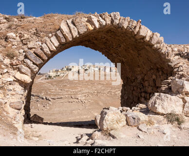 Arch of Crusader church at Kerak (Karak) Castle in Jordan framing new town in distance - Stock Photo