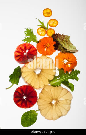 Cross section of peeled citrus fruit and greens back lit on white - Stock Photo
