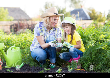 Mother and little girl planting strawberry seedlings in summer time