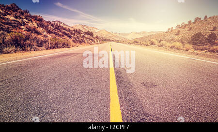 Retro vintage old film style endless country road, travel adventure concept, space for text, USA. - Stock Photo