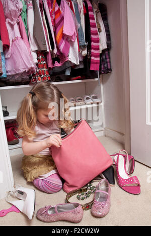 Young girl sitting in front of her closet looks in large pink purse with shoes surrounding her. - Stock Photo
