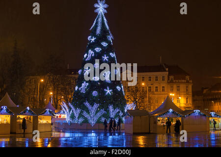 Traditional european Christmas market in Vilnius (Lithuania) at night: Christmas tree decorated with angels, snowflakes - Stock Photo