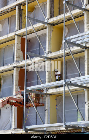 Worker wearing safety gear standing on scaffolding looking at his smart phone - Stock Photo