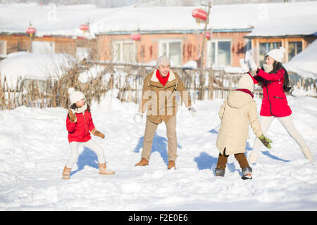 Young family having a snowball fight in the snow - Stock Photo