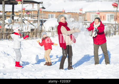 Happy family having a snowball fight in the snow - Stock Photo
