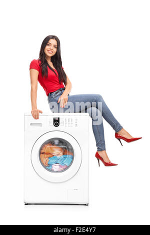 Full length portrait of a beautiful young woman sitting on a washing machine and looking at the camera - Stock Photo