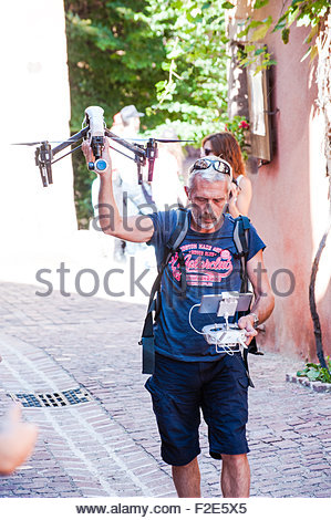 A man flying an aerial quadcopter drone in a small village in France, Riquewihr Photographed by an Photographer - Stock Photo