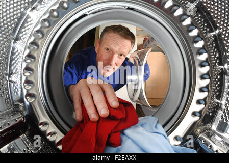 man taking washing out of washing machine - Stock Photo