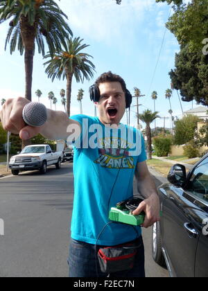 Los Angeles, California, USA. 11th Sep, 2015. DJ Flula Borg poses with his mixing console and microphone on a street - Stock Photo