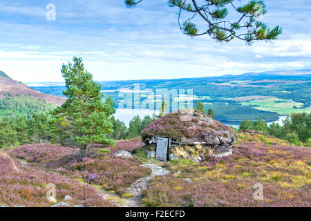 ABRIACHAN TRAIL OR WALK ABOVE LOCH NESS  THE SHIELING HUT  SURROUNDED BY PURPLE HEATHER  IN LATE SUMMER AND VIEW - Stock Photo