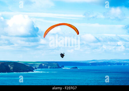 a paraglider along the coastline near st,agnes head in cornwall, uk - Stock Photo