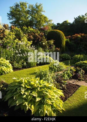 Chenies Manor; portrait view of sunken garden in afternoon sun with fresh green plants in well tended borders and - Stock Photo