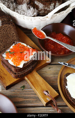 Bread with red caviar on a cutting board, food - Stock Photo
