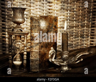 Magic book, firing candle and hourglass on vintage table - Stock Photo