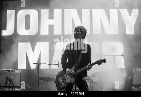 Johnny Marr singing and playing guitar at Victorious Festival 2015 with a backdrop saying 'Johnny Marr'. - Stock Photo