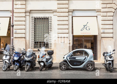 The Renault TWIZY  an electric car parked between motorbikes in a small space Rome Italy Roma Lazio Itlay EU Europe - Stock Photo