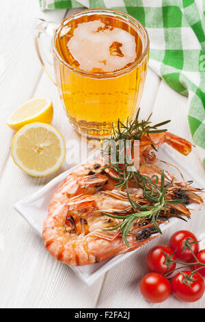 Beer mug and grilled shrimps on wooden table - Stock Photo