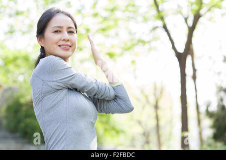Happy mature woman exercising in park - Stock Photo