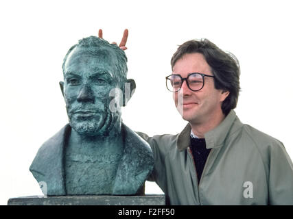 A man jokingly adds devil horns to a bronze bust of author John Steinbeck on display outdoors at Cannery Row, a - Stock Photo