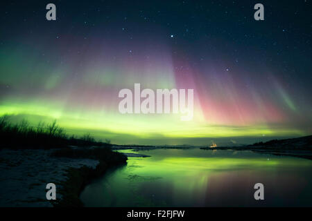 Northern lights blazing in the sky over lake Thingvallavatn in Thingvellir national park in Iceland - Stock Photo