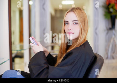 Portrait woman texting with cell phone in hair salon - Stock Photo