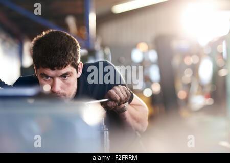 Mechanic working in auto repair shop - Stock Photo