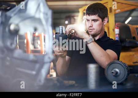 Mechanic examining part in auto repair shop - Stock Photo