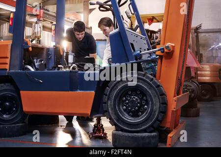Mechanics examining forklift in auto repair shop - Stock Photo
