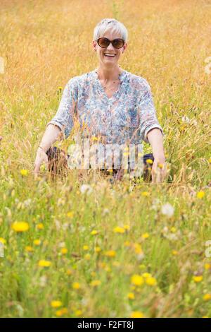 Portrait senior woman sitting cross-legged in rural field - Stock Photo