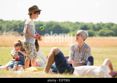 Multi-generation family in sunny field - Stock Photo