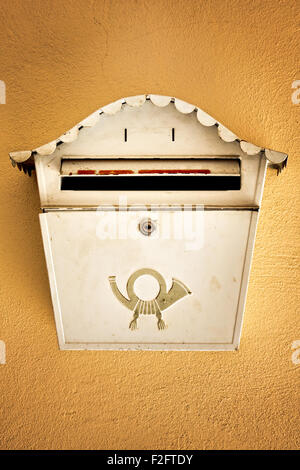 Old ancient mail box on brown wall - Stock Photo