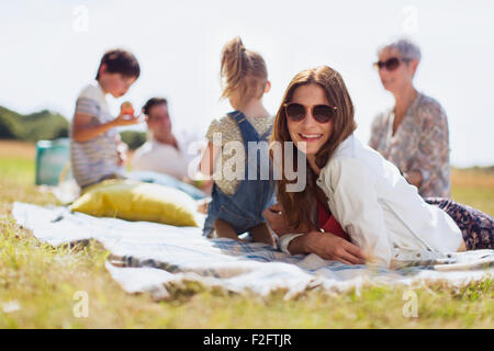 Portrait smiling woman laying on blanket in sunny field with family - Stock Photo