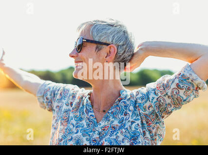 Enthusiastic senior woman with arms outstretched in sunny field - Stock Photo