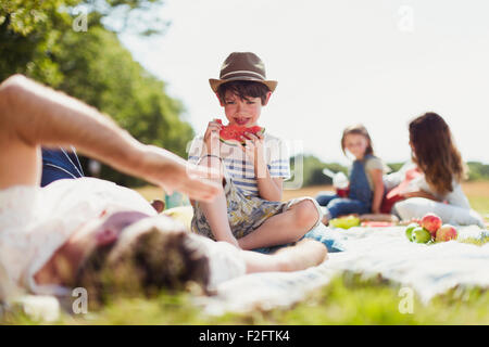 Smiling boy eating watermelon on blanket in sunny field - Stock Photo