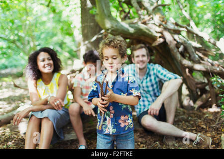 Family watching boy play with sticks in woods - Stock Photo