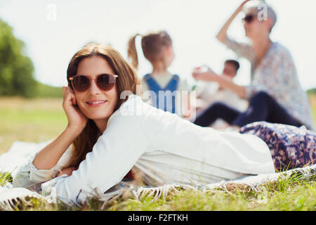 Portrait smiling woman laying on blanket in sunny field - Stock Photo