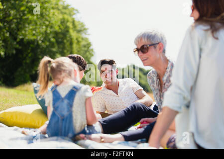 Multi-generation family relaxing on blanket in sunny field - Stock Photo