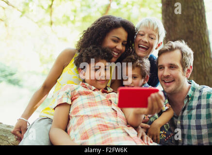 Multi-generation family taking selfie with camera phone in woods - Stock Photo