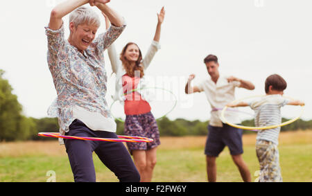 Playful multi-generation family spinning in plastic hoops in field - Stock Photo