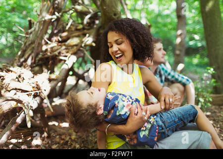 Playful mother and son in woods - Stock Photo