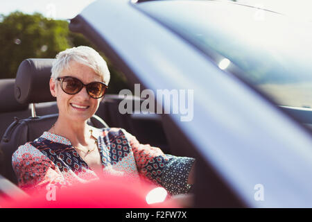Portrait smiling senior woman in sunglasses driving convertible - Stock Photo