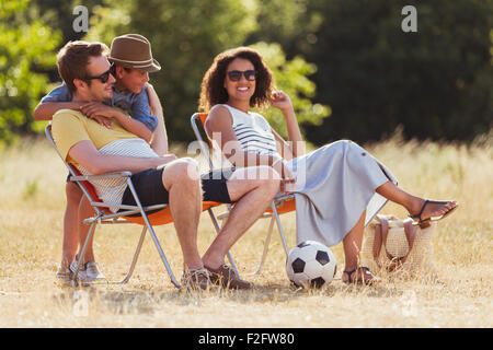Smiling family relaxing in sunny field - Stock Photo