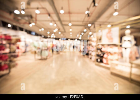 out of focus shot from the inside of a department store, showing the womens clothing department - Stock Photo