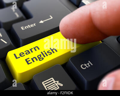 Learn English Button. Male Finger Clicks on Yellow Button on Black Keyboard. Closeup View. Blurred Background. - Stock Photo