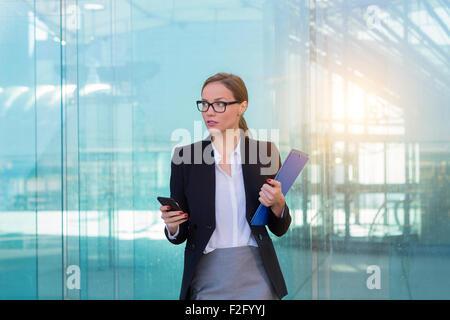 Businesswoman using a smart phone - Stock Photo