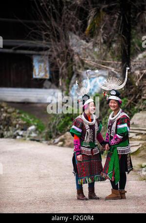 Young women of Miao Long Skirt minority wearing traditional costumes and silver jewellery, Jidao village, Guizhou, - Stock Photo
