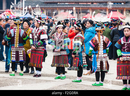 Young women of Miao Long Skirt minority in the traditional costumes and silver jewellery dancing to the sounds of - Stock Photo