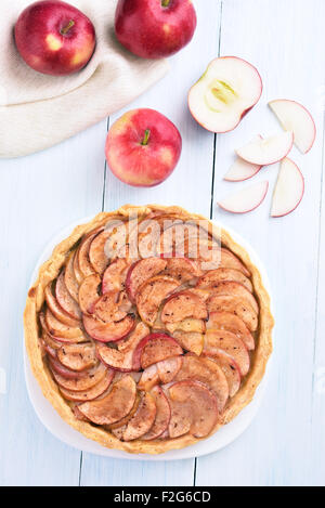 Fruit pie and fresh apples on wooden table, top view - Stock Photo