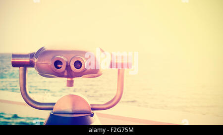 Vintage toned photo of a binocular pointed at horizon, future concept, copy space. - Stock Photo